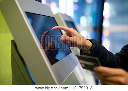 Woman using credit card on automatic ticketing machine