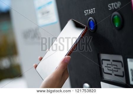 Woman use cellphone for payment car charging machine