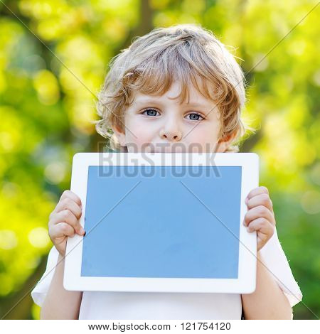 Funny blond kid boy holding tablet pc,