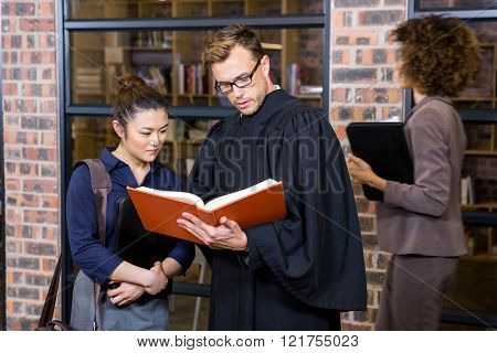 Lawyer and businesswoman reading law book in office