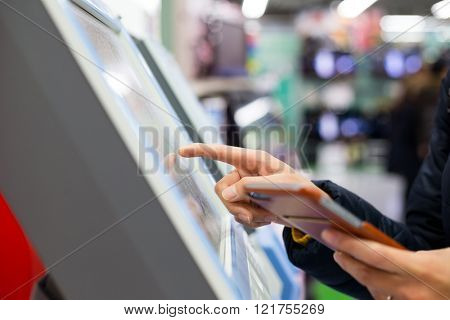 Woman touch on the ticketing machine with cellphone