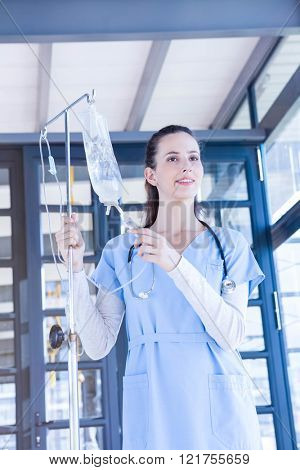 Portrait of doctor holding intravenous drip in hospital
