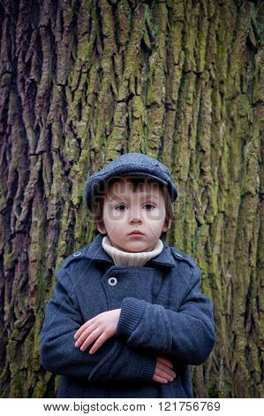Close Portrait Of A Little Boy In The Forest, Standing Next To A Tree