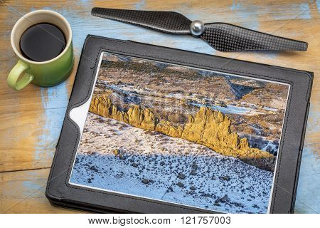 aerial photography concept - reviewing aerial picture on a digital tablet with a drone rotor propeller and a cup of coffee - rock formation in Rocky Mountains foothills