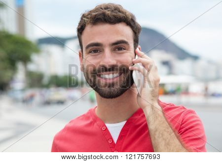Handsome Man With Red Shirt At Cellphone In The City