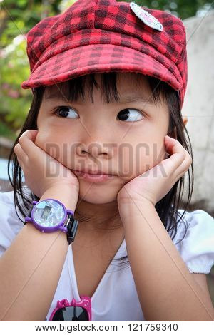 Asian Little Girl Sitting His Hand On Chin
