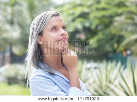 Thinking Caucasian Woman With Blue Blouse In A Park