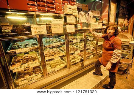 HONG KONG, CHINA - FEB 7: Elderly female seller of street bakery with cakes and buns for a late dinner on February 7, 2016. More than 47 million tourists visit Hong Kong annually