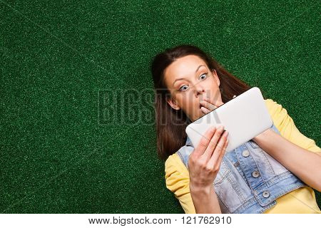 Surprised woman with digital tablet