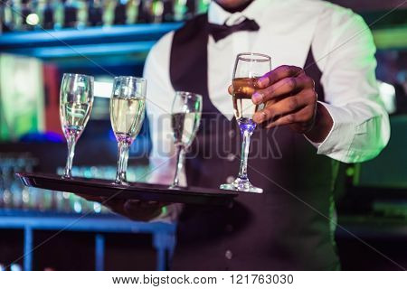 Bartender holding a tray of glasses and serving champagne in bar