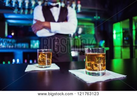Two glasses of whiskey on bar counter and bartender standing in background