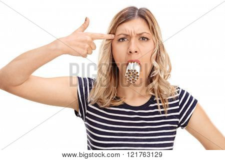 Blond woman with a bunch of cigarettes in her mouth holding a hand gun on her head isolated on white background