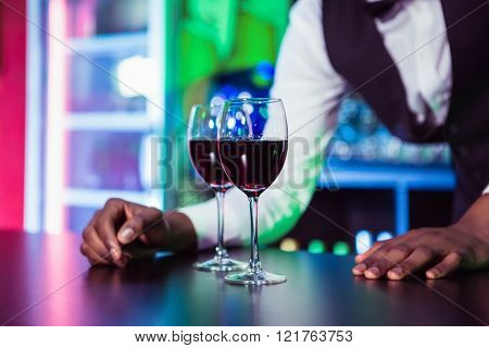 Two glasses of wine on bar counter and bartender leaning in background