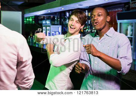 Group of men dancing near bar counter in bar
