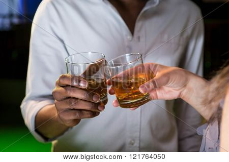 Couple toasting their whisky glasses in bar