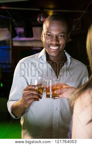 Portrait of beautiful man smiling while toasting his whisky glass in bar