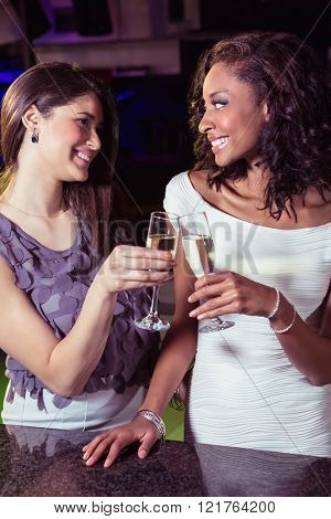 Young women toasting champagne flutes at bar counter in bar