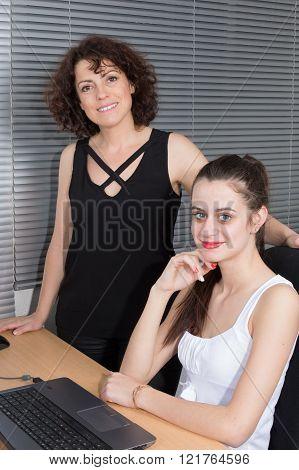 Two Business Woman Analyzing Balance Sheet On Computer