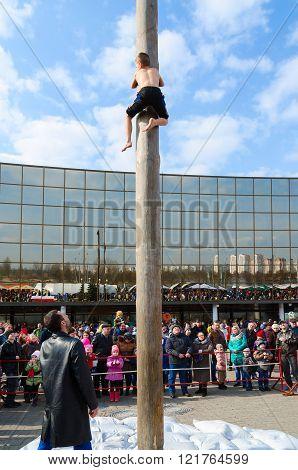 Boy Climbs On Pillar Behind Gift During Shrovetide Entertainments
