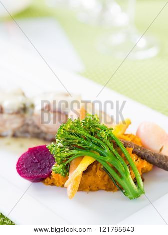 Blanched vegetables on a white rectangular plate.