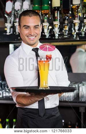 Portrait of bartender serving cocktail at bar counter