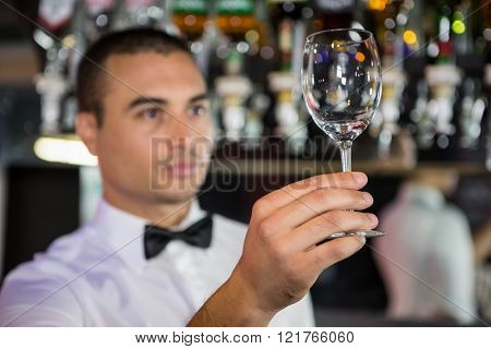 Barkeeper checking a wine glass after cleaning