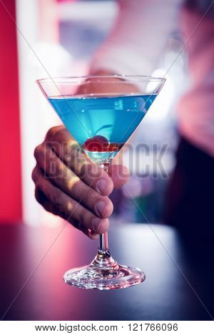 Bartender serving a blue martini in bar