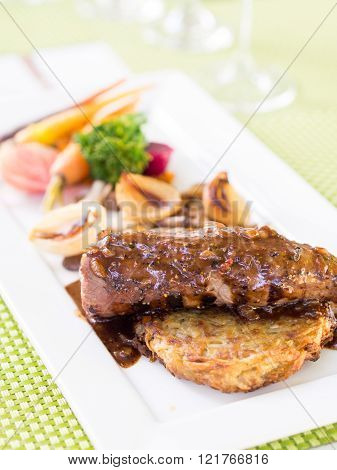 Impala schnitzel in black pepper sauce served with potato pancake and blanched vegetables.