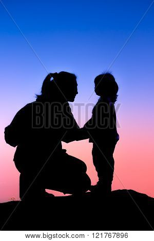 Silhouette side view of young mother and child hikers enjoying the view at the top of a mountain. Colorful sunset sky background. Friendly family.