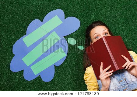 Young woman is lying down on a grass ,hiding behind  book and thinking about something with a though