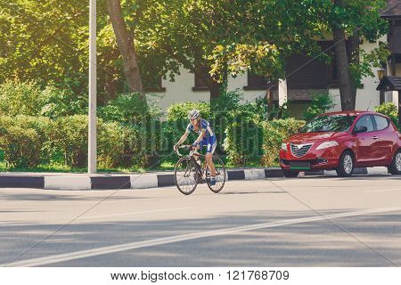 Female cyclist rides a racing bike on city road