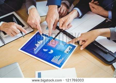 Businesspeople discussing the chart and graph in the meeting