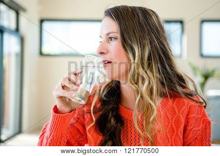 distracted woman drinking a glass of water in the sitting room