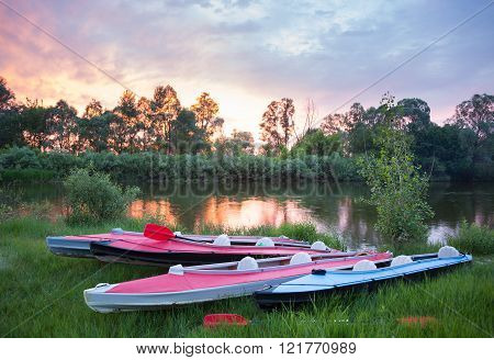Red and blue kayaks near a river in beautiful nature at sunset