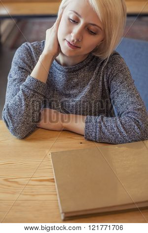 Woman Young Beautiful Student With The Album Thinking About  Ideas Sitting At The Table