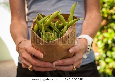 unrecognizable person holding a paper bag of freash geen beans