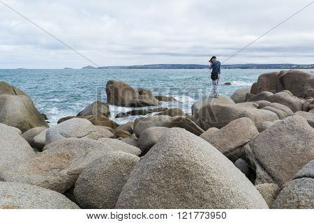 Port Elliot South Australia Australia - March 12 2016. A middle aged adult male photographer on the Rocks at Port Elliot South Australia pointing towards the ocean.