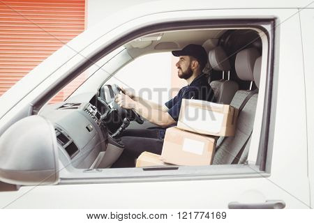 Delivery man driving his van with a package on the front seat