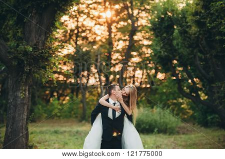 Beautiful romantic wedding couple of newlyweds hugging in park on sunset