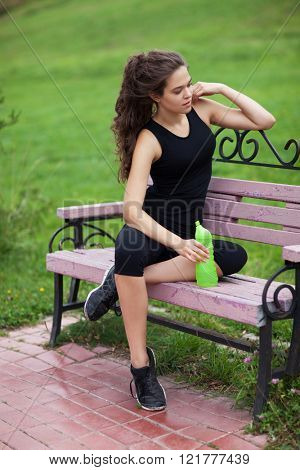 Young beautiful woman in sportwear sitting on the bench