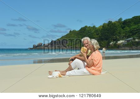 elderly couple on beach with coconut