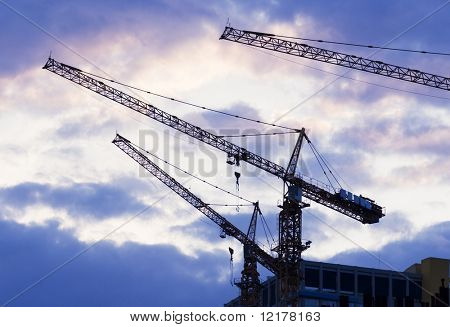 Building with elevating crane and clouds on background