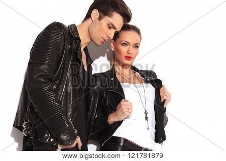 side view of a fashion couple in leather jackets standing in studio and look away from the camera, man is looking down, woman is pulling her jacket's collar