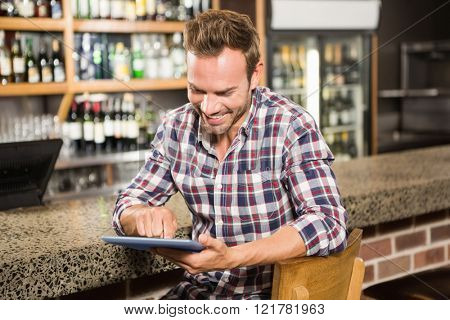 Handsome man using tablet computer in a pub