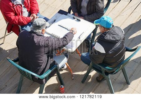 old men playing a game of domino