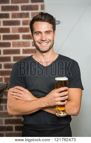Handsome man holding a pint of beer in a pub