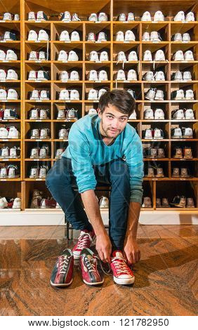 Man, sitting on a stool, trying on bowling shoes in front of wooden selves with an array of different sizes leather shoes