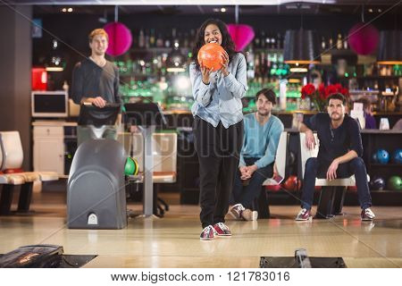 Young black woman holds the bowlingball up to throw it, with her friends in the background