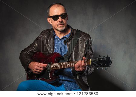 portrait of seated mature man in leather jacket and sunglasses, playing his electric guitar while looking away from the camera in gray studio background