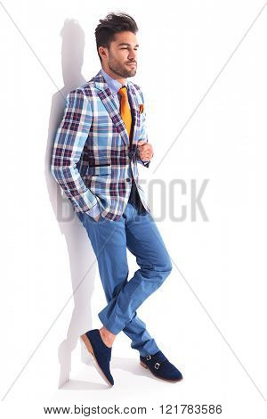 smart casual man standing with legs crossed and hand in pocket in studio background while looking away from the camera